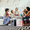 Group of diverse women sitting together at baby shower of female friend. Smiling young pregnant woman celebrating baby shower with best friends.